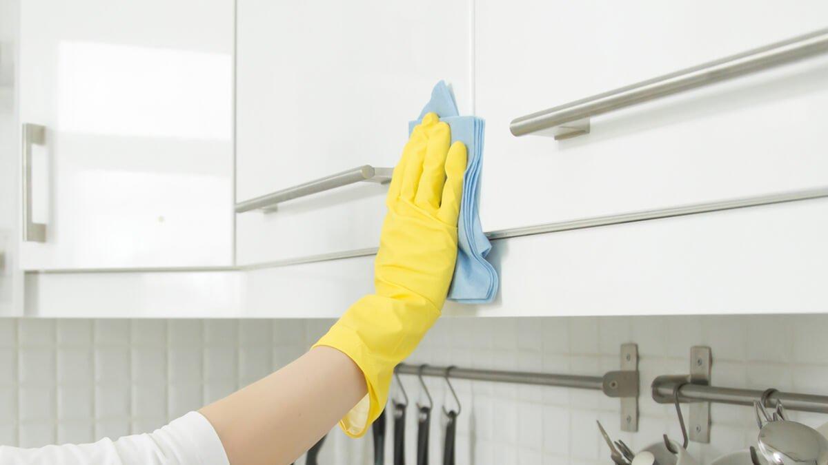persona limpiando armarios de cocina