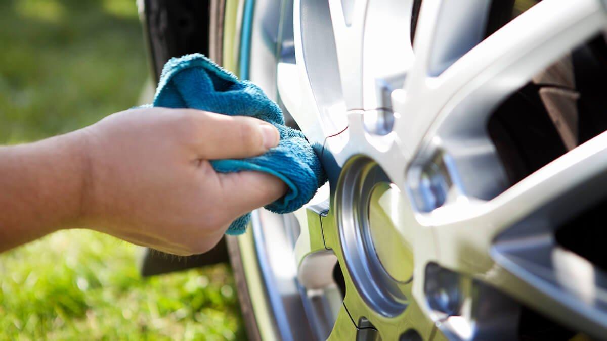 persona limpiando llanta del coche